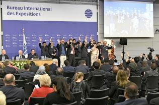 2025年万博の開催国を決めるBIE総会の最終プレゼンテーションで、壇上で手を振る日本の誘致委員会メンバーら(23日、パリ)=共同