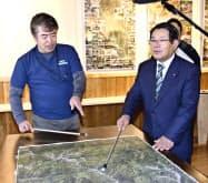 東峰村災害伝承館で展示を見る渋谷博昭村長(右)と九大の三谷泰浩教授(24日午後)=共同
