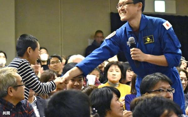 報告会で子供と握手する宇宙飛行士の金井宣茂さん(25日午後、千葉県市川市)=共同