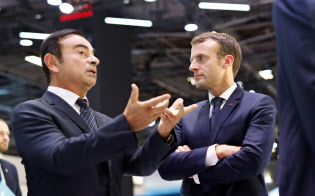 10月3日、パリモータショーでマクロン仏大統領と話すカルロス・ゴーン元日産会長=AP