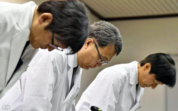 記者会見で謝罪する京都大病院の稲垣暢也病院長(中央)ら(26日)=共同