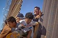 米国への不法入国を図ろうとする移民集団(25日、メキシコ北西部ティフアナ)=ロイター