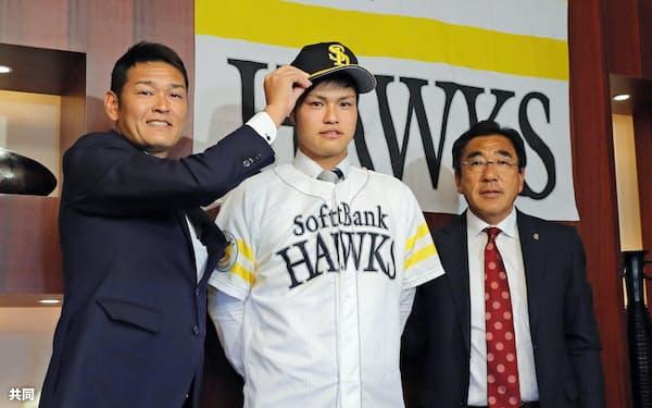 入団に合意し、ソフトバンクの担当者に帽子をかぶせてもらうドラフト1位の甲斐野央投手=中央(27日、東京都内のホテル)=共同