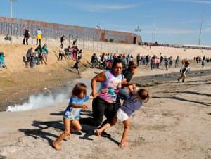 不法に米国境を渡ろうとした移民が米側から催涙ガスを発射された(25日、メキシコ北西部ティフアナ)=ロイター