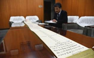 金剛組の成り立ちが記された巻物を広げる刀根社長(大阪市天王寺区)