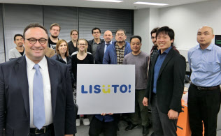 LISUTOは社員の9割が外国人。矢頭潤一さん(右から2人目)はニール・プラテック社長(手前)の下、外国人社員とともに働く(東京都港区)