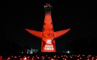 太陽の塔に映された万博決定を祝う文字(29日午後、大阪府吹田市の万博記念公園)=松浦弘昌撮影