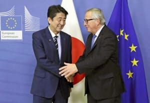 ユンケル欧州委員長(右)と握手する安倍首相(18日、ブリュッセル)=代表撮影・共同