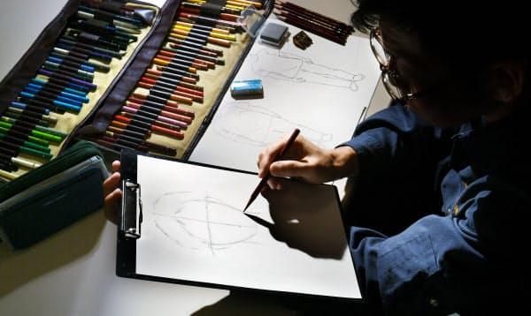 犯人の似顔絵を描く練習をする技能員