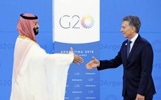 30日、G20を前にアルゼンチンのマクリ大統領(右)の出迎えを受けるサウジアラビアのムハンマド皇太子(ブエノスアイレス)=共同