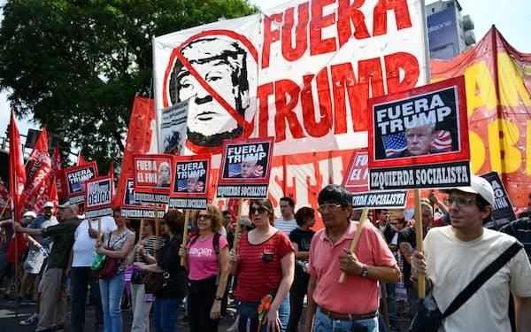 「トランプは出て行け」と書かれた旗などを掲げG20首脳会議に反対する市民ら(30日、ブエノスアイレス)