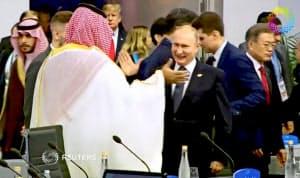 30日、G20会議でムハンマド皇太子とハイタッチするプーチン大統領(ブエノスアイレス)=ロイター