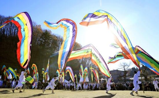 「木幡の幡祭り」で、鮮やかな5色の旗「五反幡」などを持って駆けだす白装束の男たち(2日、福島県二本松市)=共同
