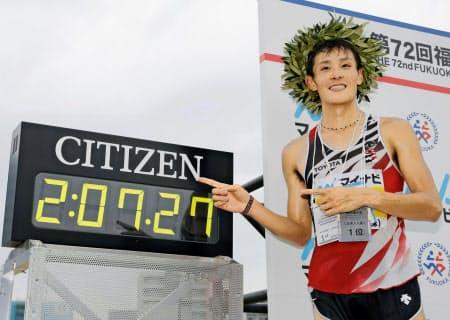 2時間7分27秒で初優勝し、タイムを指さす服部勇馬(2日、平和台陸上競技場)=共同