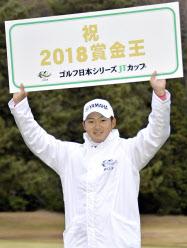 今季の賞金王となり、ボードを掲げる今平周吾(2日、東京よみうりCC)=共同