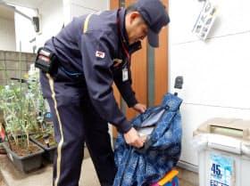 玄関先で置き配専用のバッグに荷物を入れる