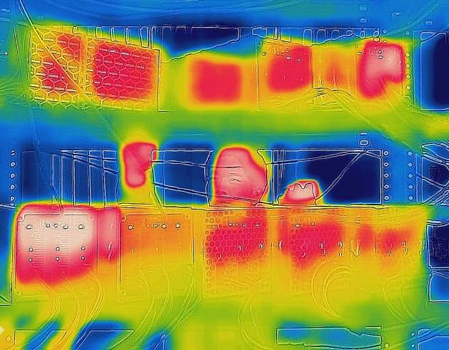 サーモグラフィーカメラで撮影した仮想通貨のマイニングマシン。熱を帯びた部分が赤く染まる(石川県加賀市)