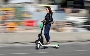 スペイン・マドリードでシェアスクーターに乗る女性=ロイター