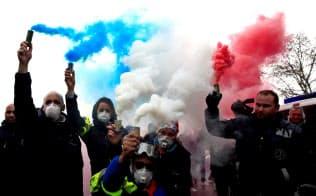 3日、青、白、赤(仏国旗の3色)の煙をたいてパリのデモに参加する救急車の運転手=ロイター