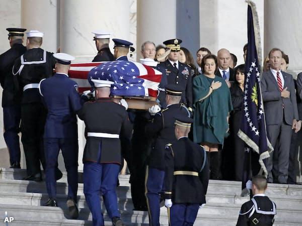 星条旗で覆われ、運ばれるジョージ・H・W・ブッシュ氏の遺体を納めたひつぎ=3日、米ワシントン(AP=共同)
