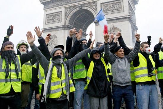 シンボルである「黄色いベスト」を着用しパリの凱旋門前に陣取るデモ参加者ら(1日)=ロイター
