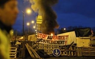 5日、仏西部のル・マン市で燃料倉庫を封鎖するデモ隊。政府は4日、燃料増税の6カ月延期を発表したが、抗議デモは収まっていない=AP