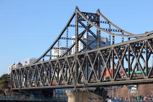 橋に並ぶトラックの列も頻繁に見られるようになった(奥が中国)
