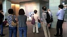 ガスコージェネで発電した電気で映るテレビを食い入るように見つめる避難者ら(9月、札幌市のアーバンネット札幌ビル)