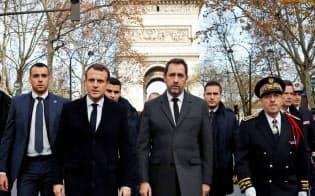 抗議デモの翌日、消防隊や警察官を訪問するために現れたマクロン大統領(左から2人目)ら(2日、パリ)=ロイター
