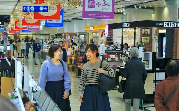 シニア客の多い京王百貨店新宿店の化粧品売り場で買い物を楽しむ若い女性客(東京都新宿区)