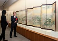 紅花屏風の前で話す山形銀行の長谷川吉茂頭取(右)(山形美術館)