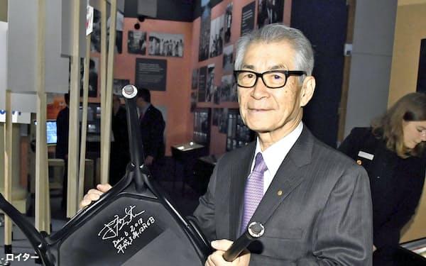ストックホルムのノーベル博物館でサインした椅子を持つ本庶佑・京大特別教授(6日)=ロイター