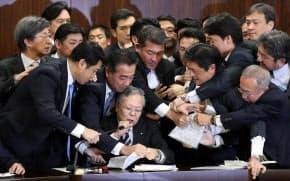 参院法務委で入管法改正案の採決を宣言する横山委員長を守る与党議員と抗議する野党議員(8日未明)