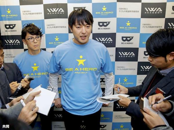 イベントに参加後、記者に囲まれる巨人入りが決まった岩隈久志投手(8日、大阪市)=共同