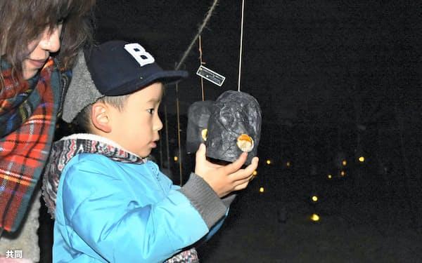 「多可・冬のホタル2018」で点灯されたあんどんを見つめる子供(8日夜、兵庫県多可町)=共同