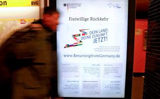 本国帰還を望む難民への資金支援を訴える独政府のポスター(11月、ベルリン)=ロイター