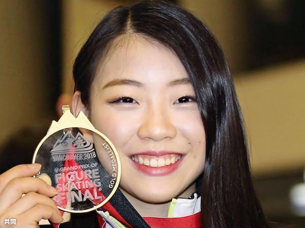 フィギュアスケートGPファイナルで優勝し帰国、金メダルを手に笑顔の紀平梨花選手(11日午後、成田空港)=共同