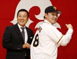 入団記者会見後、ユニホームを着てポーズを取る巨人の丸佳浩外野手(右)と原辰徳監督(11日、東京都内のホテル)=共同