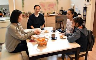 戸建て型の民泊施設で住人の日本人女性(左)と交流するタイ人一家(11日、東京都世田谷区)
