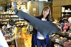 なめしたサメ革を持つ熊谷牧子社長(10月、宮城県気仙沼市)=共同