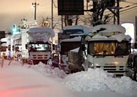 記録的な大雪で立ち往生し、国道8号に停車したままの車の列(2月、福井県坂井市)=共同