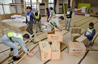 岡山県倉敷市が運営している真備町地区の避難所「まきび荘」を片付ける市職員(13日午前)=共同