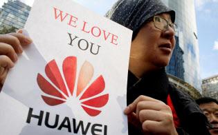 11日、カナダのバンクーバーで、副会長兼CFOが逮捕されたファーウェイへの支持を表明する中国人男性=ロイター