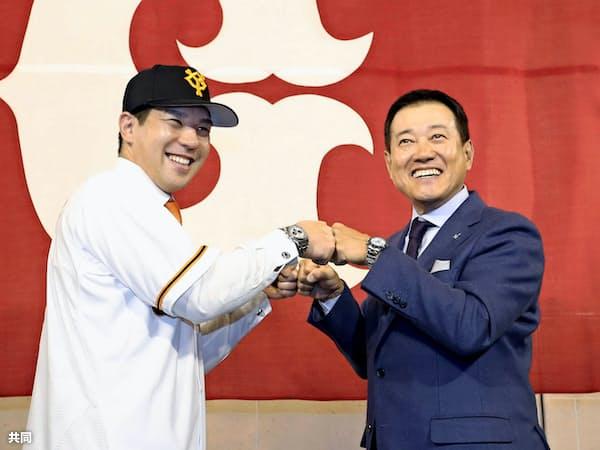 巨人の入団記者会見で原辰徳監督(右)とグータッチをする炭谷銀仁朗捕手=共同