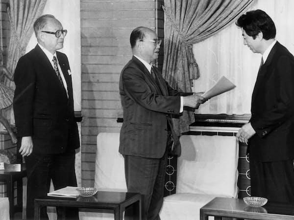 1993年10月、首相官邸で細川護煕首相(右)に地方分権推進基本法の制定などを答申する行革審の鈴木永二会長(中央)