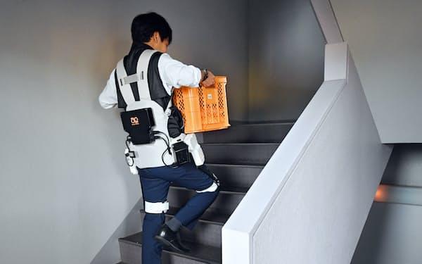 アシストスーツを装着し、コンテナを運ぶ記者(和歌山市)