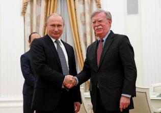 10月23日、モスクワで会談し、握手をするロシアのプーチン大統領(左)と米国のボルトン大統領補佐官(ロイター=共同)