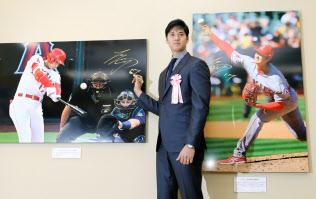 報道写真展で自身が写った写真にサインする米大リーグの大谷翔平選手(18日午前、東京都中央区)