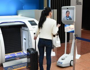 羽田空港での実証実験では、業務スタッフが遠隔操作したアバターロボット(右)で旅行者を案内した