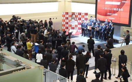 ステージで記念撮影するソフトバンク関係者。シャッター音が東証内に響いた(19日午前10時21分、東京都中央区)